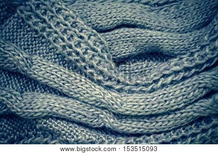 Grey knitting wool texture background. Warm knitted scarf texture. Knitted sweater background. Autumn cozy background. Woolen knitting background. Roving Wool Knit Texture. Top view.