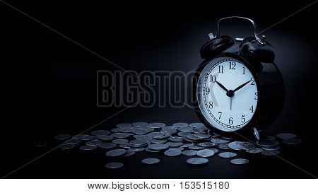 saving time Alarm clock with coins isolated on black background. with vintage filter