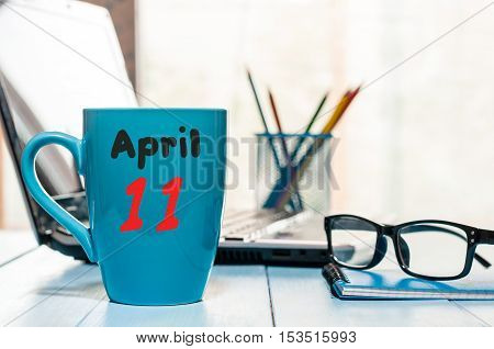 April 11th. Day 11 of month, calendar on business office background, workplace with laptop and glasses. Spring time, empty space for text.