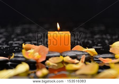 Yellow rose petals with candle and therapy stones