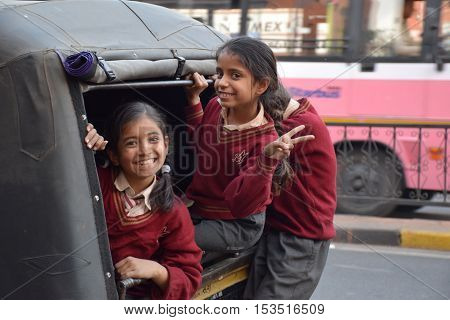 JAIPUR, RAJASTHAN, INDIA - FEBRUARY 05, 2016 - Three unidentified indian kids smiling in front of the camera inside a small truck before going to school