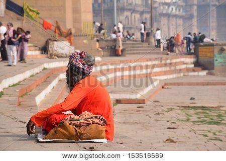 VARANASI, UTTAR PRADESH, INDIA - FEBRUARY 17, 2016 - Unidentified indian man sitting and meditating on the ghats of Varanasi after sunset