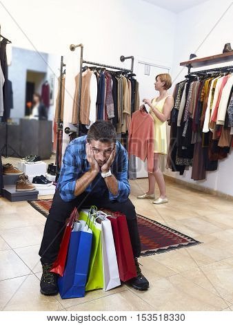 young couple shopping with man tired and bored holding lot of bags and woman happy looking for dress buying clothes at fashion store in relationship and shopaholic concept