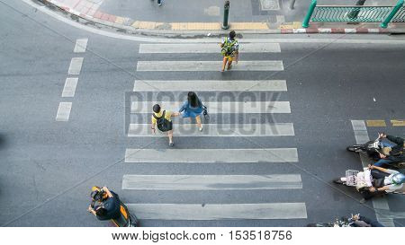 Top view of people are moving across the pedestrian crosswalk in the city street (Aerial photo)
