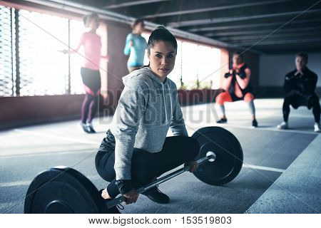 Fit healthy woman exercising sitting at floor looking at camera getting ready to lift weight