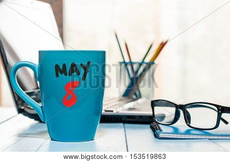May 8th. Day 8 of month, calendar on morning coffee cup, business office background, workplace with laptop and glasses. Spring time, empty space for text.