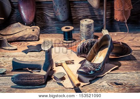 Cobbler Workshop With Tools, Leather And Shoes