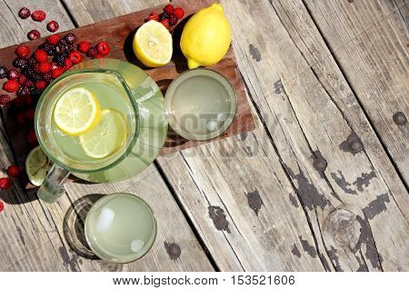 A pitcher full of fresh squeezed lemonade is sitting on a wood picnic table background surrounded by red respberry fruit on a summer day.