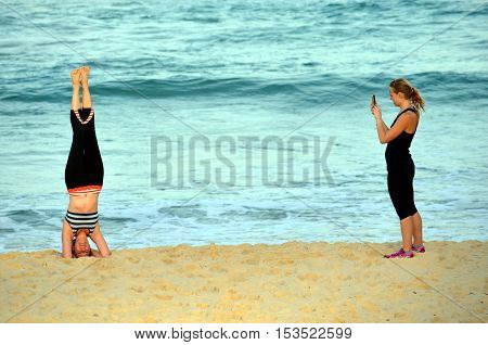 Sydney Australia - Jun 9 2013. Woman standing on her head and doing yoga on the beach. Another girl taking photos. Woman practices Ashtanga Vinyasa yoga Surya Namaskar Sun Salutation asana