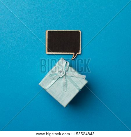 top view of small gift box on blue background with wooden black chalk board speech bubble for text