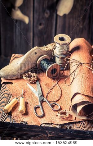 Aged Cobbler Workshop With Tools, Leather And Shoes