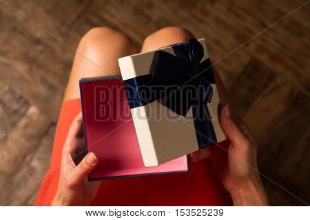 Horizontal top view woman opening a present with blue ribbon on her knees