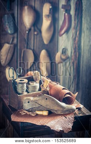 Small Shoemaker Workshop With Tools, Shoes And Leather