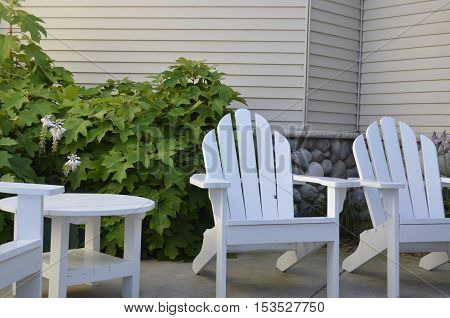 White Adirondack Chairs on the patio in the courtyard