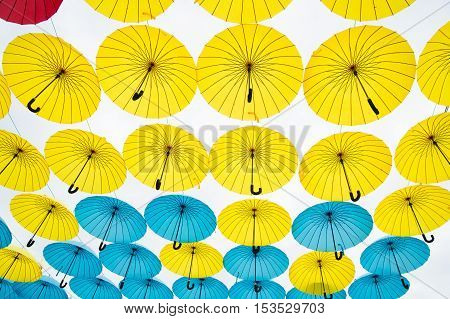 Collection of multi colored umbrellas hanging up in an open position over a street offering shade and protection from the elements.