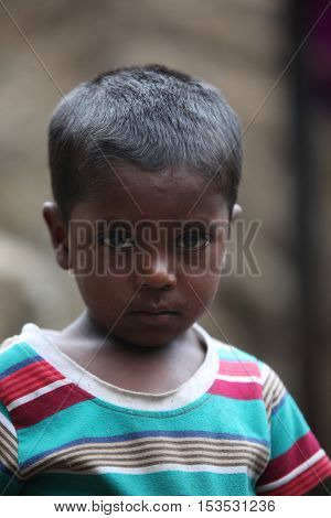 A portrait of a poor Indian boy looking with a sad face.