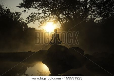 Silhouette of a beautiful Yoga woman in the morning at the hot spring park