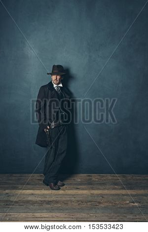 Mysterious Mature Retro 1900 Western Man Standing Against Gray Wall.