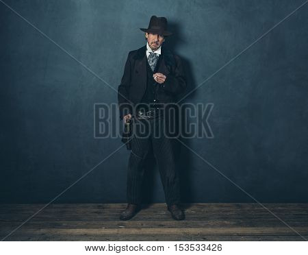 Retro Mature 1900 Western Man Standing With Cigarette Against Gray Wall.