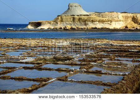 A peaceful bathing coastal resort in Gozo with salt pans in the foreground