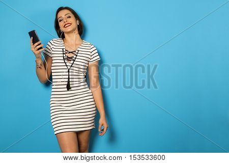 Beautiful Brazilian Girl Enjoying Music With The Head Phones In Blue Background