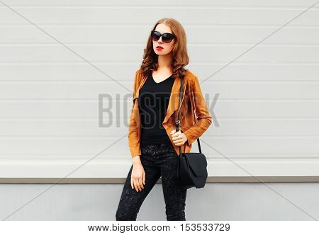 Fashion Pretty Woman Wearing A Sunglasses Brown Jacket Black Handbag Over Grey Background