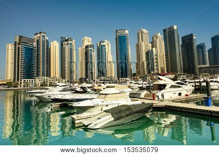 DUBAI, UAE - OCTOBER 09, 2016. View of skyscrapers in Dubai marina with skyscrapers from the Marina Walk with reflections and yachts