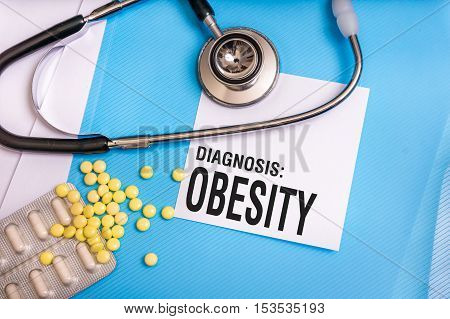 Obesity Word Written On Medical Blue Folder With Patient Files