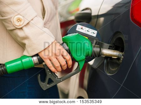 Woman fills petrol into her car at a gas station closeup