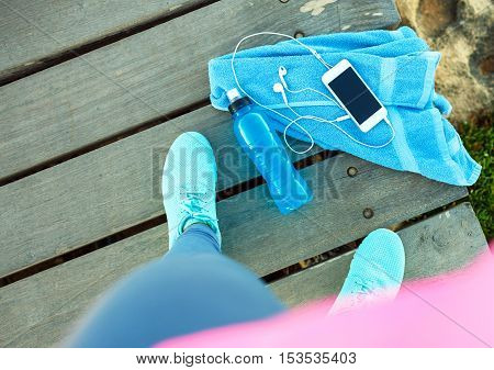 Top view of a sports girl that is resting after a morning run. Necessary accessories - towel bottle of water smart phone headphones