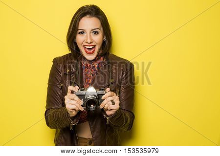 Fashion Young Girl Makes The Photo With Old Camera. Yellow Background