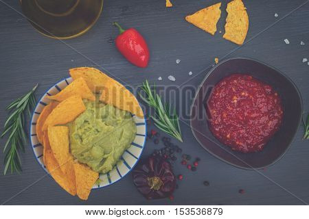 Green guacamole sause with crispy corn chips and pepper salsa sause, retro toned