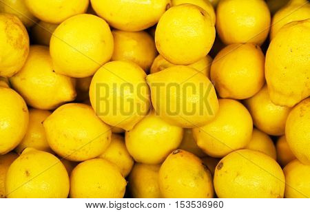 Lot Of Bright Yellow Lemons In Supermarket.