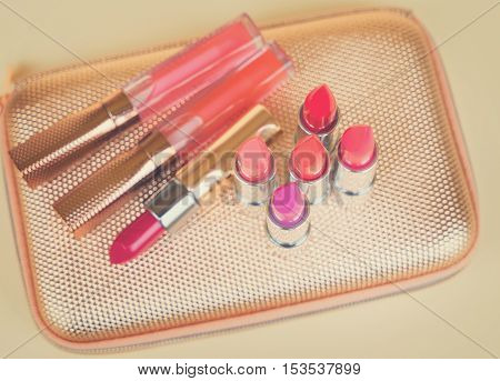Collection of colorful lipsticks on golden woman pursue, retro toned