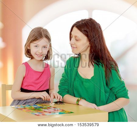 Clever little girl and her teacher at the table laid out cards with pictures.In a room with a large semi-circular window.