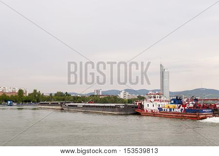 Vienna / Austria - July 21st 2014: Picture of Mercur 201 romanian cargo boat pushing two barges on the Danube river in front of the Millenium Tower