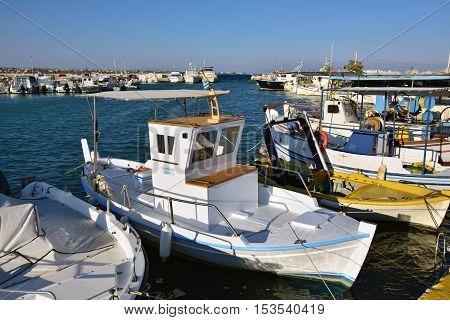 Artemis Greece - Sept 28 2016: Small fishing boat moored near pier at sunny warm evening. Aegean sea