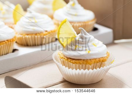 Lemon cupcakes with white cream, cupcake packaging, delivery box, selective focus, close up