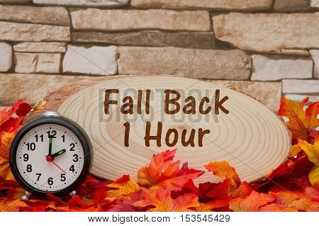 Daylight savings time message Some fall leaves an alarm clock and wood plaque on weathered brick with text Fall Back 1 hour