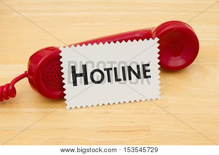 Calling to get help A retro red phone with note card on a desk with text Hotline