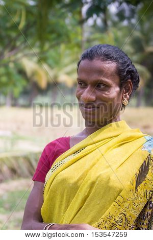 Dindigul India - October 23 2013: Smiling Hijra transgender person in a rural setting wears a beautiful yellow sari with maroon T-shirt. Her name is Sandra.