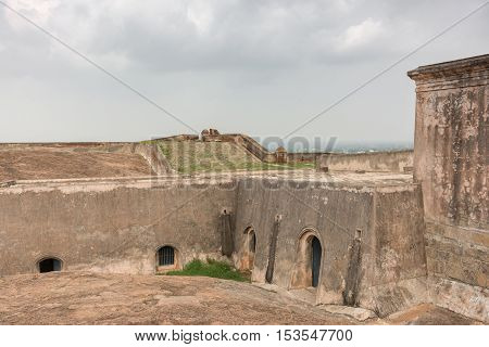 Dindigul India - October 23 2013: Underground bunker-like cellars and storerooms inside the historic Dindigul Rock fort under light blue sky. Brown-beige as dominant color.