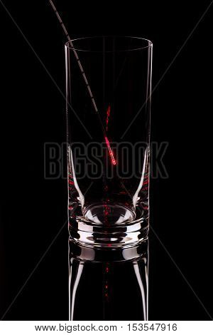 The shining probe in an empty glass on a black background