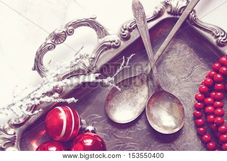 Over head view of an elegant silver serving platter, silver spoons, retro Christmas ornaments and a strand of red tree trimming beads. Snow-covered branch.