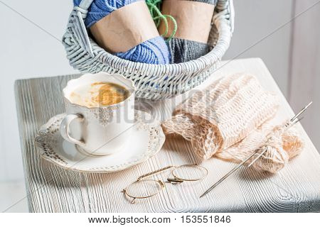 Handmade knitted scarf with color skein on white table