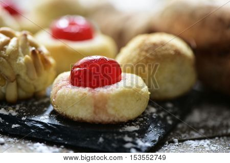 closeup of some homemade panellets, typical confection eaten in All Saints Day in Catalonia, Spain, on a rustic kitchen table