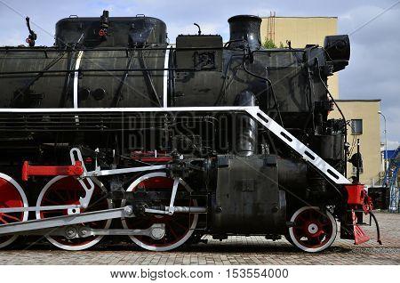 Red wheels of old black steam locomotive. Wheels of an old soviet steam train
