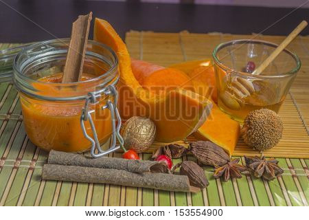 Pumpkin carrot fresh smoothie with cinnamon and spices on bamboo mat. Sweet honey. Healthy food. Copy space background. Autumn theme. Day light.