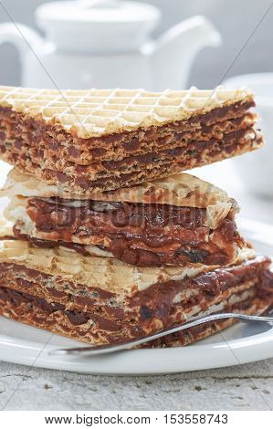 Stack of wafer sheets filled with caramelized sugar and hazelnut cream served on white plate poster
