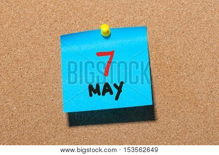 May 7th. Day 7 of month, calendar on cork notice board, business background. Spring time, empty space for text.